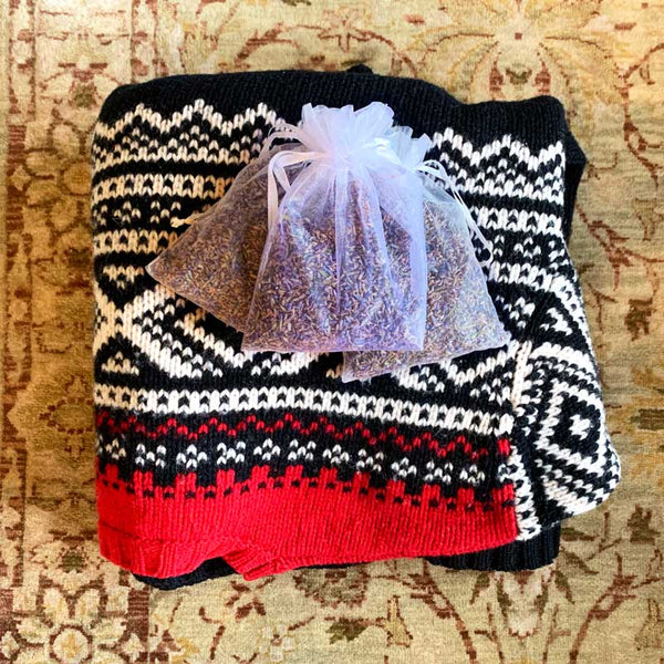 Sweater on carpet with lavender buds pouch of aromatic dried lavender