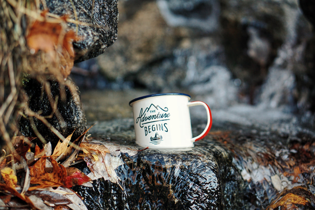 Adventure begins cup sitting on waterfall in a forest