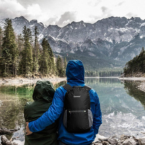 Couple standing near scenic lake with backpack on