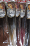 Several packets of the Yaki Minky hair extensions showing colors available