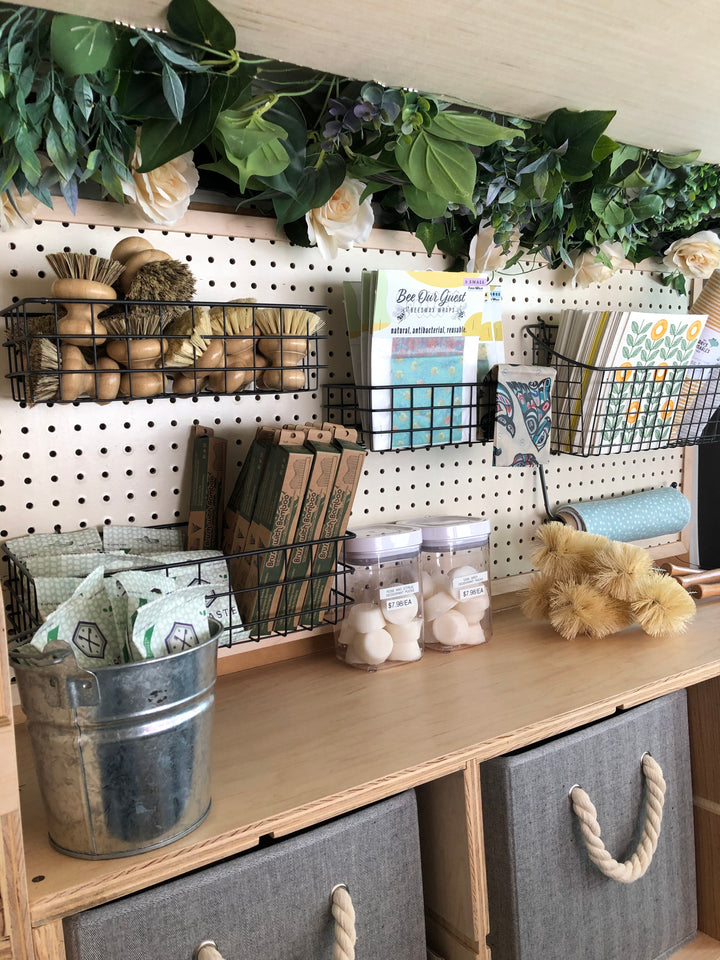 A pegboard featuring plastic free household items such as dish brushes, bees wax wraps, Swedish dish cloths, bamboo tooth brushes, and growler brushes. Above is a fake foliage arrangement