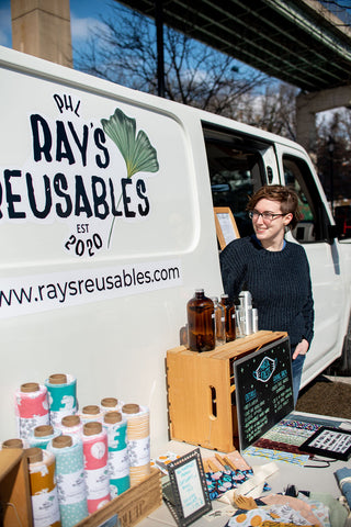 Ray stands in front of her van looking at the Ray's Reusables logo on the side
