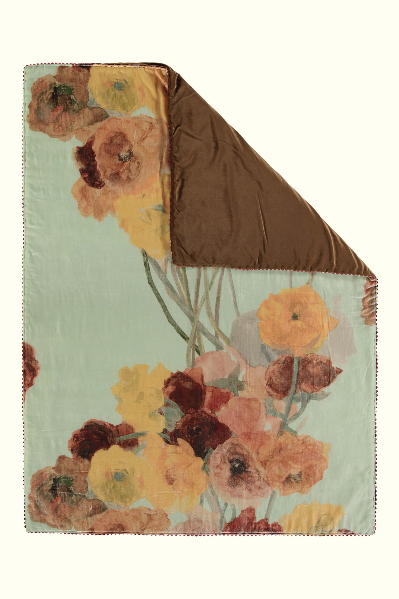 A luxury British silk velvet bed throw by GVE in mint ochre Ranunculus print design.