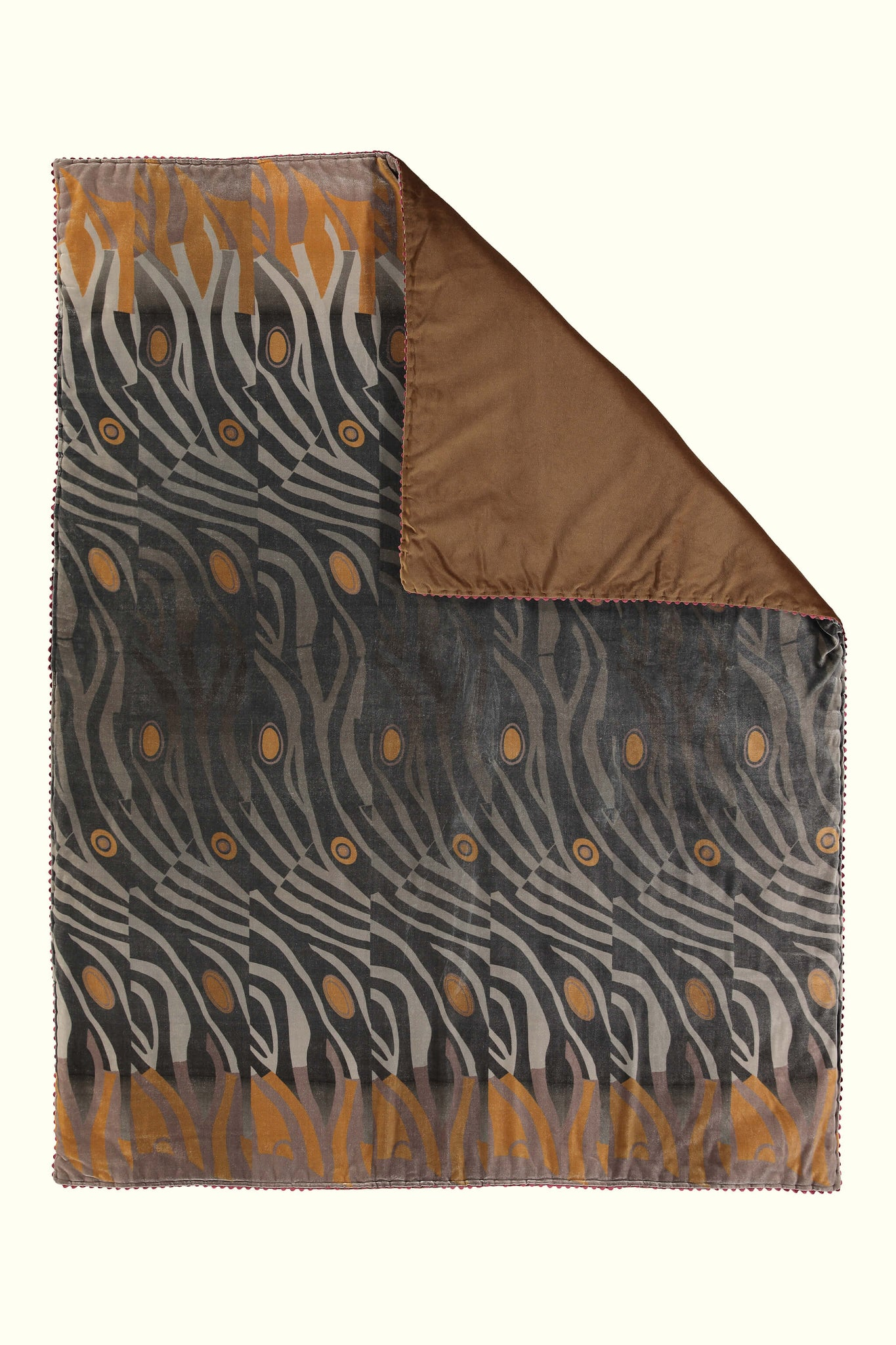 A luxury British silk velvet bed throw by GVE in black and amber Dune print design.