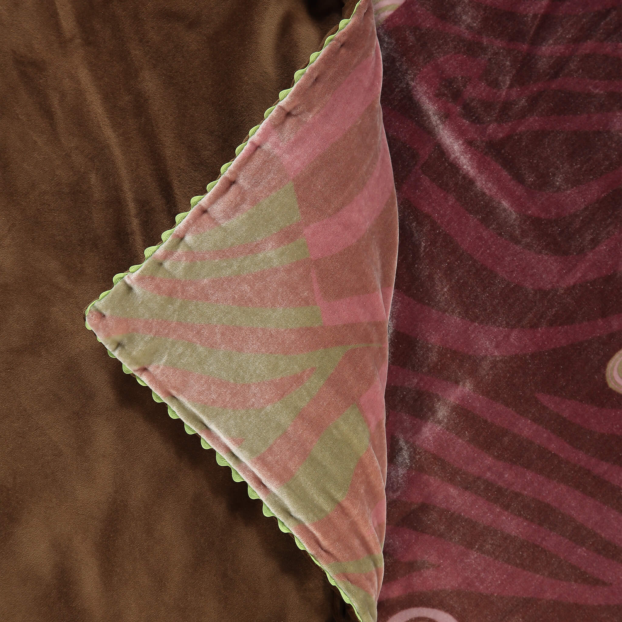 A luxury British silk velvet bed throw by GVE in rose, rust and artichoke Dune print design.