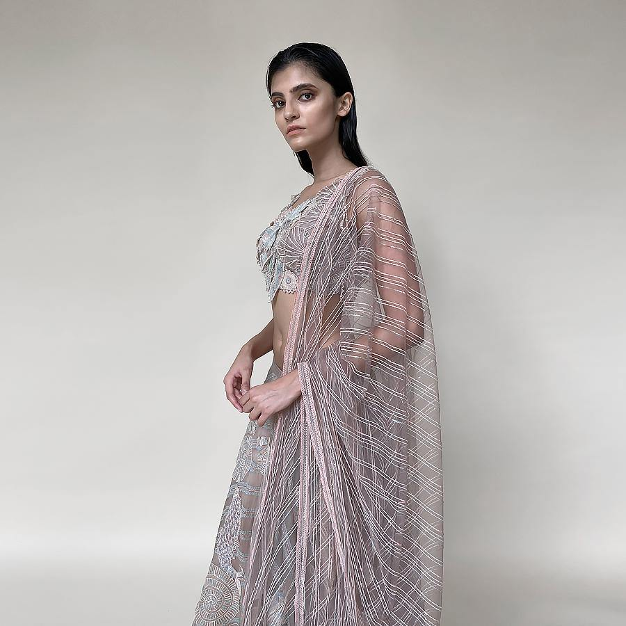 Organza silk lengha with a fine play of geometric and floral motifs with 3D embroidery and bugle bead detailing on the blouse. There is a fine play of Resham, sequin, pearl and katdana detailing. The look has playful young vibes that is perfect for someone who loves new and different vision about design. Abhishek Sharma, Abhishekstudio.