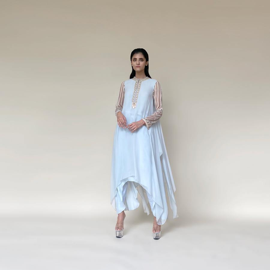 Draped asymmetrical chiffon kurta with embellished sleeves and neckline. The style is very elegant and fluid. The style is comfortable and elegant. The look is a perfect pick for someone who loves the elegance and yet like to be different. The look works perfectly for a day as well as a relaxed evening affair.