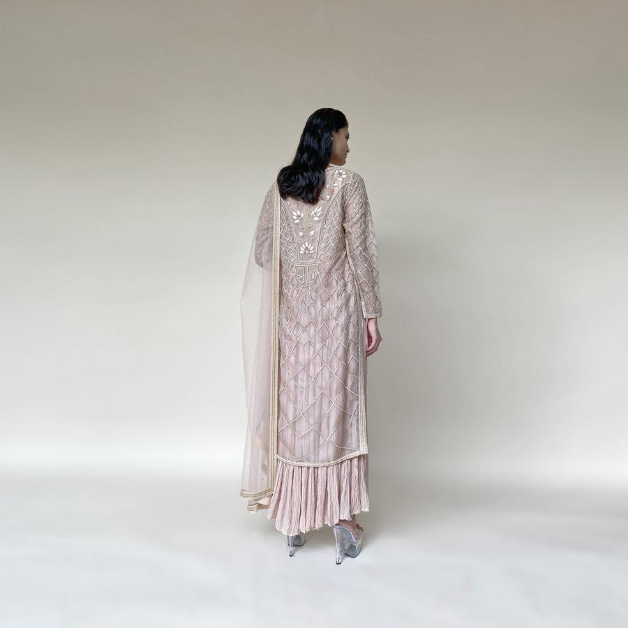Organza silk kurta with fine Gresham and velvet applique embroidery embellished with pearl and katdana. There is a separate crinkled voile inner that gives the style a layered look. Elegance and delicate details are the main focus of the look. There is an interesting play of geometrical design with a hint of floral elements. Abhishekstudio, Abhishek Sharma