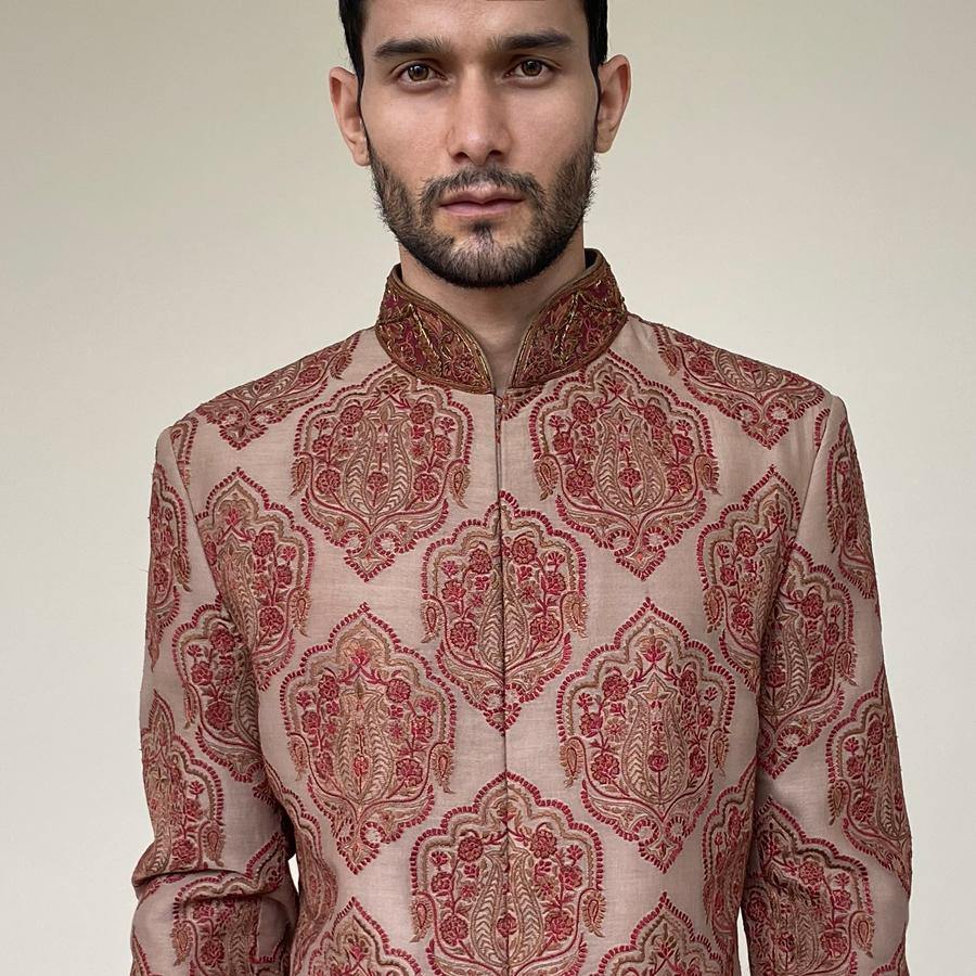 Jamavar design silk sherwani with concealed placket. Earthy Brown-burgundy thread work sherwani is embellished with contrast zardozi borders. In earthy tones, you'll discover that sherwani teams up elegantly with a semi-fitted kurta and dhoti for a royal wedding.  Abhishek Sharma, abhishekstudio