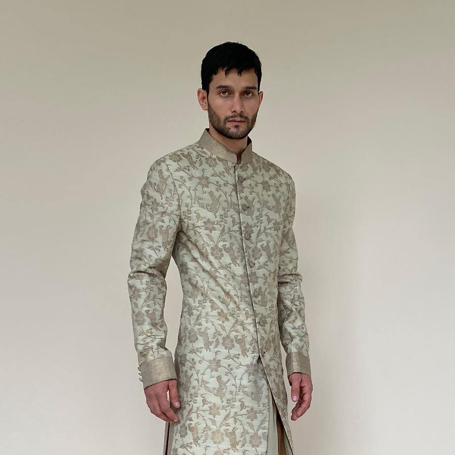 Forest weave brocade mid-calf length sherwani with a high collar. Ivory/gold animal and floral brocade sherwani is a perfect look for the day wedding or engagement ceremony. In Ivory/gold, you'll discover that sherwani teams up elegantly with a semi-fitted kurta and dhoti for a graceful monochrome which will make you look taller.  Abhishek Sharma, abhishekstudio