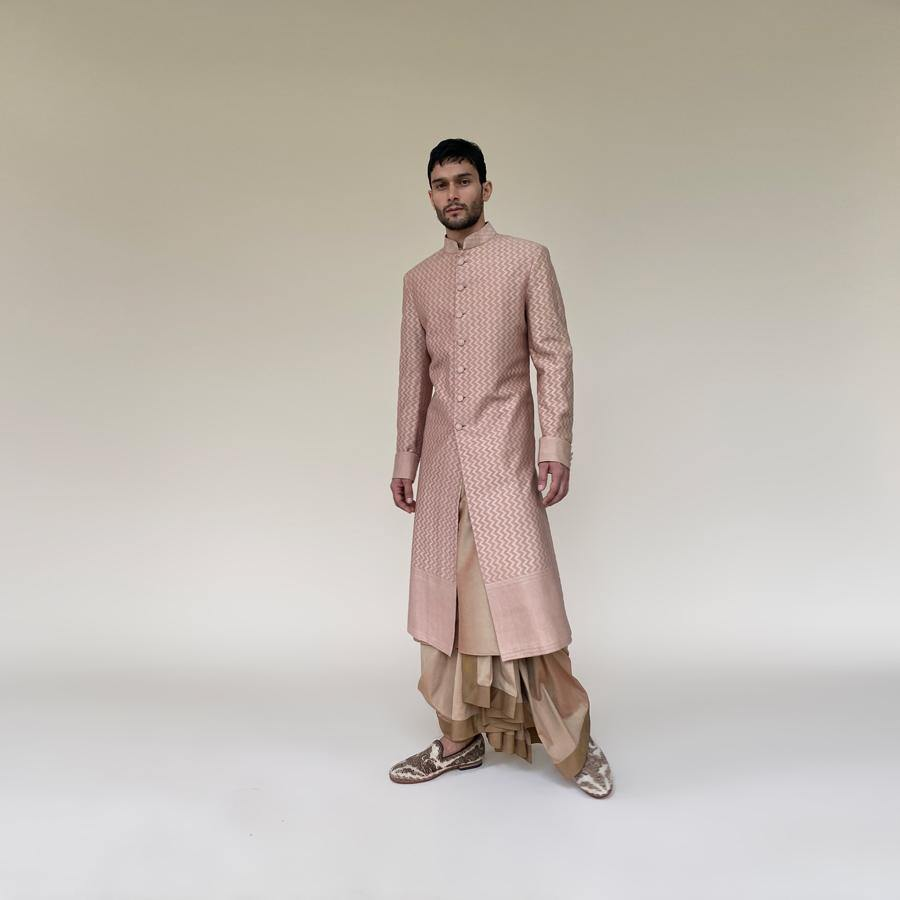 Banarasi cutwork sherwani with a vertical chevron pattern in self. Soft pink-beige wide border sherwani is a perfect look for the day wedding or engagement ceremony. In soft pink-beige, you'll discover that sherwani teams up elegantly with fitted kurta and dhoti for a graceful monochrome which will make you look taller.  abhisheksharma , abhishekstudio