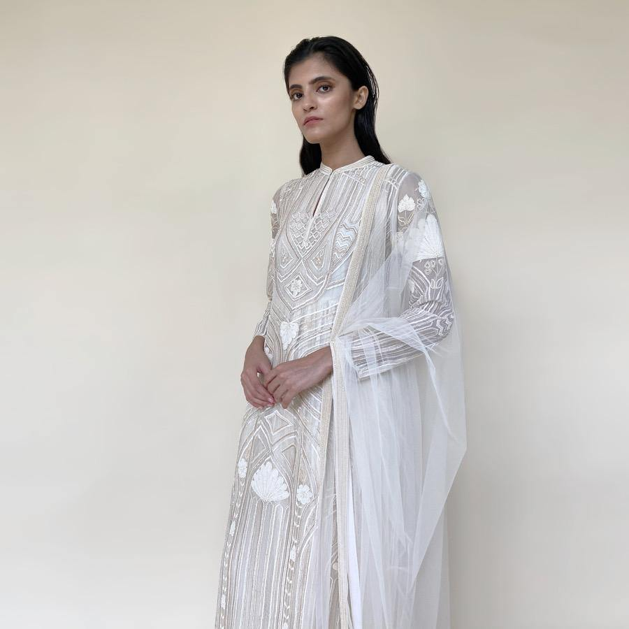 Organza silk kurta with fine Gresham and velvet applique embroidery embellished with pearl and katdana. There is a separate crinkled voile inner that gives the style a layered look. Elegance and delicate details are the main focus of the look. Abhishek Sharma, abhishekstudio