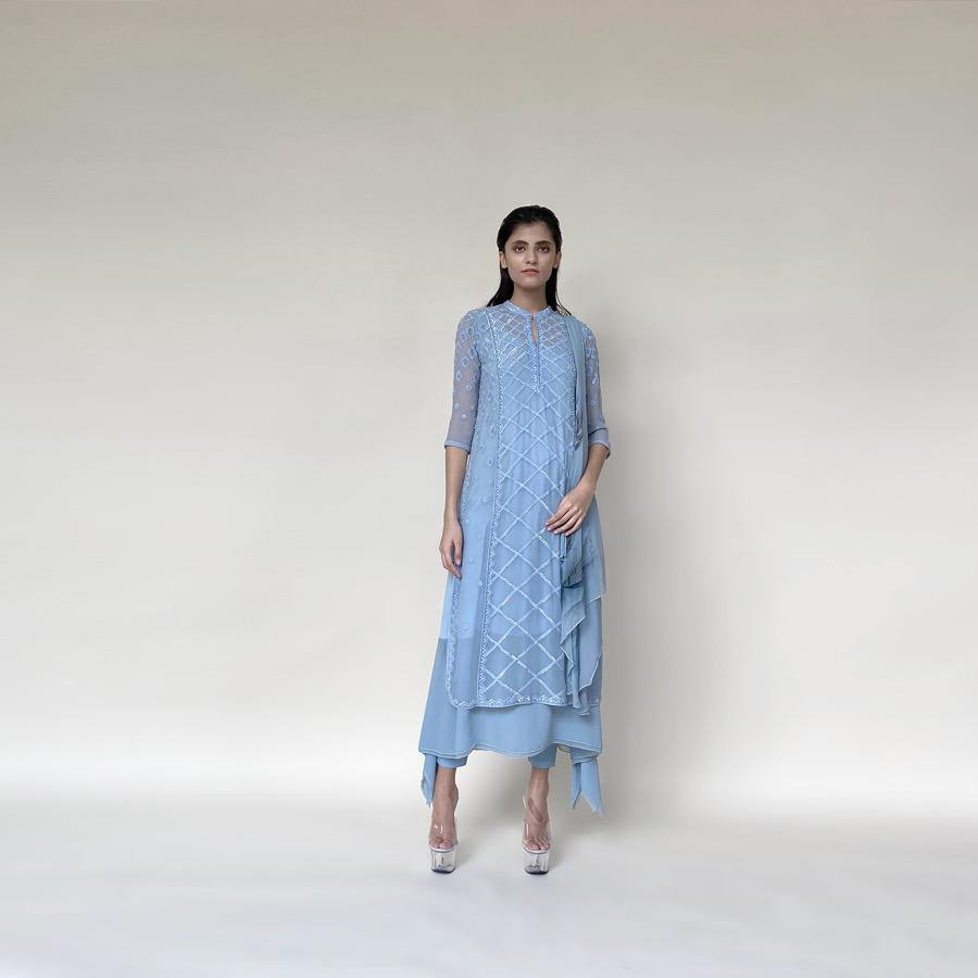 Chiffon Kalidas kurta with fine Resham shadow work and sequin embroidery. The kurta set has layered look and comes with a draped shaped stole, fitted pants and separate flared lining. The look is perfect for a refreshing and relaxed day. The look is perfect when you want to carry the grace and elegance with understated style.