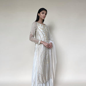 Silk organza embellished layered straight kurta with fine Resham, velvet applique and bead embroidery. The kurta has a fine voile crinkled under layer as lining giving it a layered look. there is a fine play of flower lines and geometric lines that gives the style a unique feel. The look is a perfect pick for someone who has an eye for detail and elegance. Abhishekstudio, Abhishek Sharma.