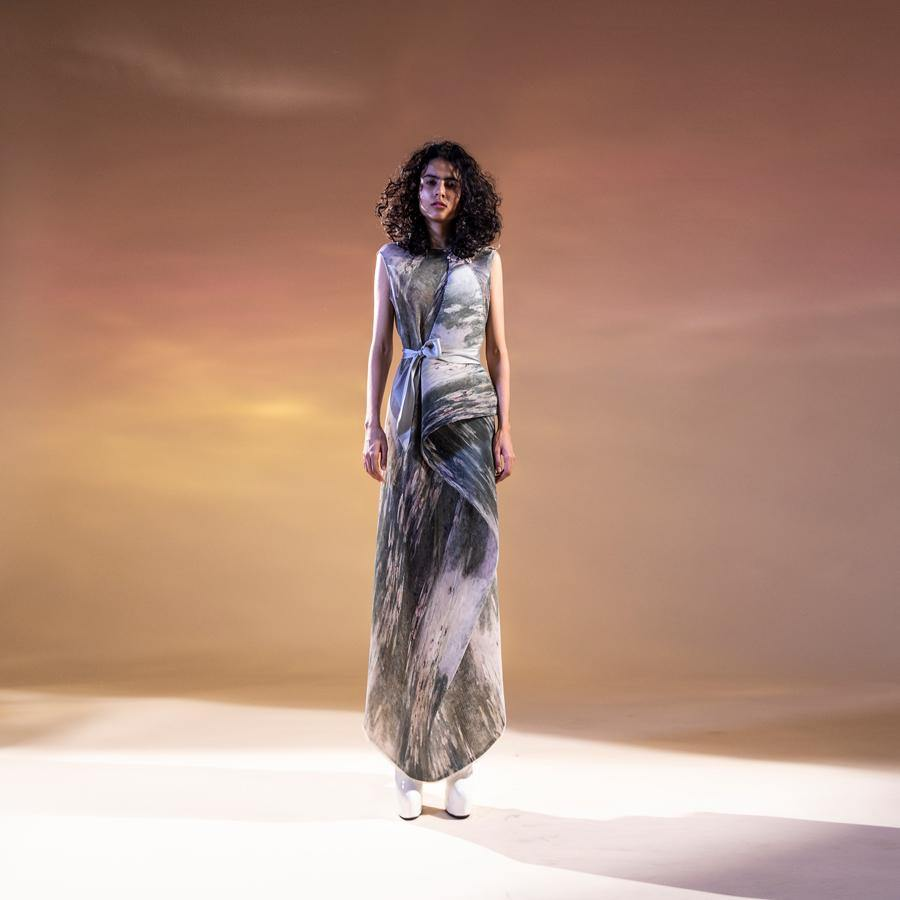 Abhishek Sharma's fresh-off-the-runway collection features unconventional drapes with printed textures. Impressionist printed textured georgette draped dress with placement embroidery in fine Gresham, sequin and bead. The dress has a satin tie-up waist belt to accentuate the waist. It's a perfect look for a day that can even work for a relaxed evening. Abhishekstudio, abhishek Sharma.