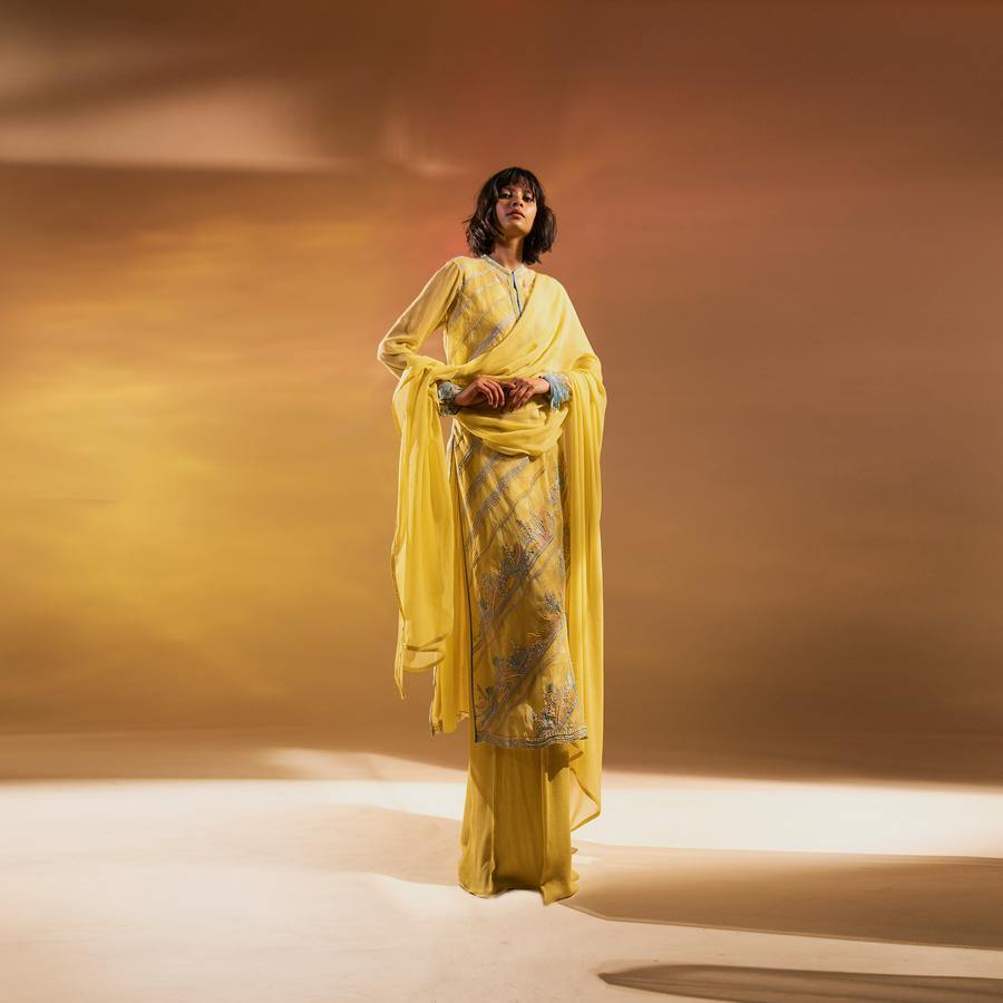 Silk organza embellished straight kurta with play of graphic lines. The kurta has a classic elegant cut with narrow mandarin collar and full sleeves. The kurta is teamed up with wide pants and chiffon dupatta. The kurta has flared inner and high side slits. Abhishek Sharma, abhishekstudio