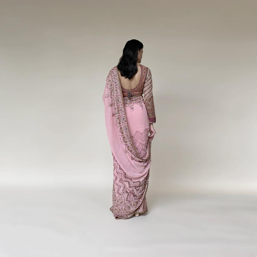 Chiffon saree with intricate net applique and fine Resham, sequin and katdana embroidery. The saree has a beautiful play of geometric and floral Mughal motifs that makes its artwork stand out. the blouse has a shaped yoke-style that connects the style to the royal vintage era with a geometric pattern on the sleeves. Abhishek Sharma, abhishekstudio