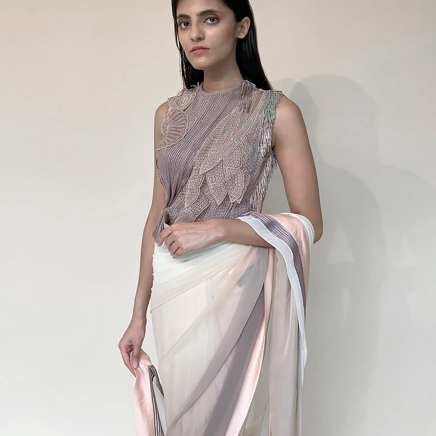 Chiffon saree ombre dyed in grey/peach/ivory pastel hues. Saree is finished with contrast satin border and satin texture embellishment. Jewel neck blouse is meticulously embellished with a mix of satin texture, thread work applique and bugle beads. Saree has a very unconventional look and feel making it a perfect pick for someone who loves contemporary. Abhishek Sharma, abhishekstudio