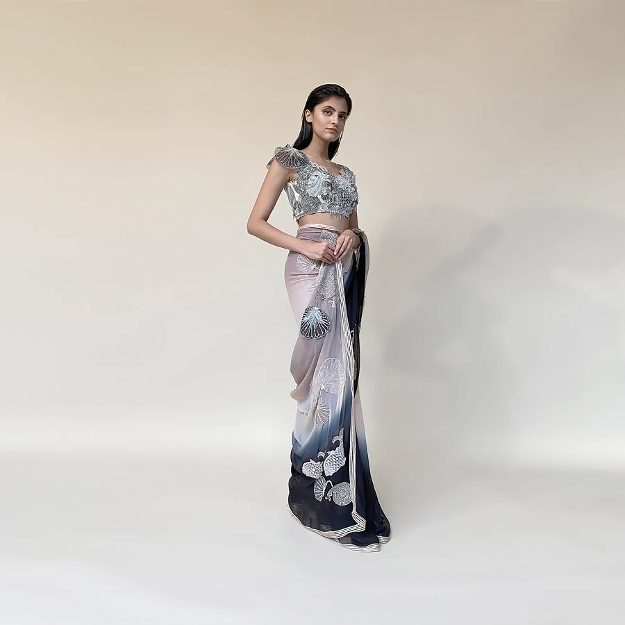 Chiffon saree ombre dyed in grey/peach/black hues. Saree is finished with contrast satin border and satin texture embellishment. Jewel neck blouse is meticulously embellished with a mix of 3D placement embroidery in thread, pearl, sequin and bugle beads. Saree possess elegance and grace as an underling feel with a dramatic play of colours and bold motifs.  Abhishek Sharma, abhishekstudio