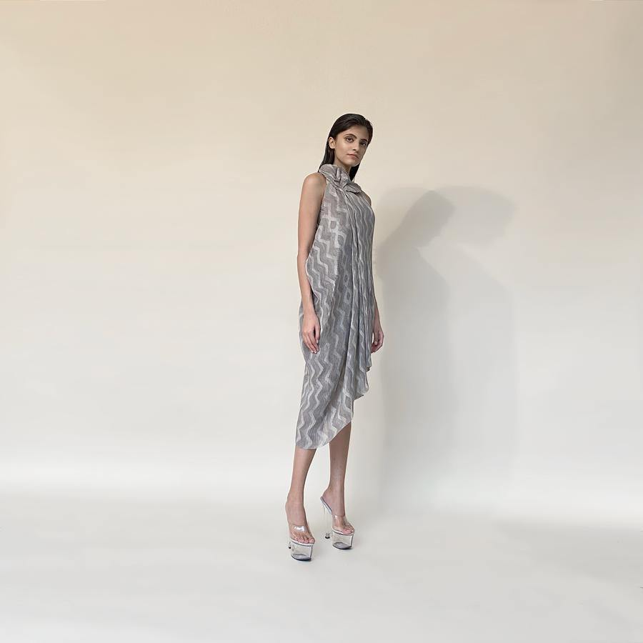 Chevron batik print pleat textured fluid draped georgette dress. It has draped ruffles around boat neck . It has a very fluid and elegant feel inspite of being an anti fit silhouette. The sleeveless draped cowl dress has very strong and dramatic vibe to it. abhishek sharma, abhishekstudio