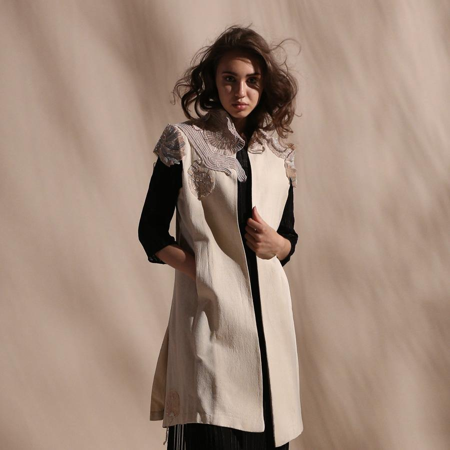 Ivory boyfriend jacket with playful square armholes. Sleeveless jacket features double vents and open front for a slightly relaxed look. Mid-length handloom silk jacket is embellished with abstract impressionist embroidery appliqué.  abhisheksharma , abhishekstudio