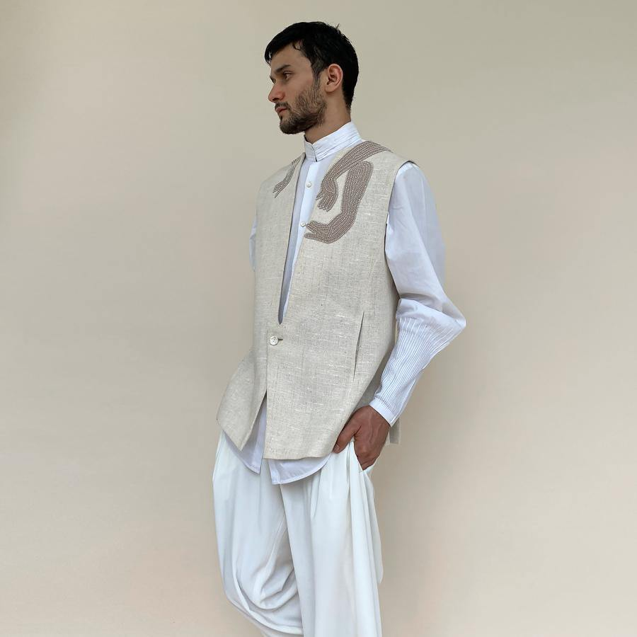 Single button closure bundi with round raised neckline. Cotton khadi texture bundi is embellished with abstract hand pattern embroidery appliqué in thread and pearl.  abhisheksharma , abhishekstudio