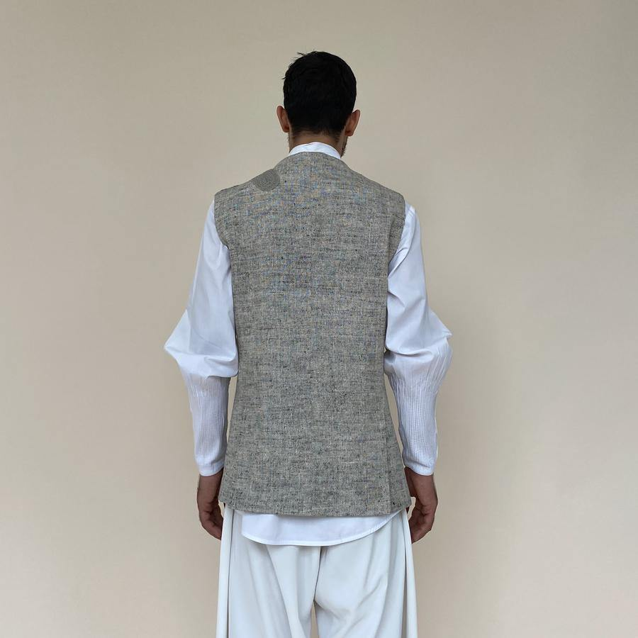 Load image into Gallery viewer, Single button closure bundi with round raised neckline. Cotton khadi shot texture bundi is embellished with abstract hand embroidery appliqué in thread and katdana.  abhisheksharma , abhishekstudio