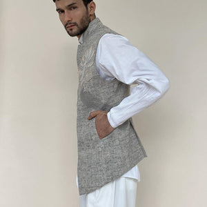 Load image into Gallery viewer, Shaped mandarin collar bundi with Single button closure and concealed metal zipper. Cotton khadi shot texture bundi is embellished with sequin lotus embroidery applique.  abhisheksharma , abhishekstudio