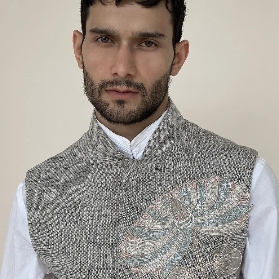 Shaped mandarin collar bundi with Single button closure and concealed metal zipper. Cotton khadi shot texture bundi is embellished with sequin lotus embroidery applique.  abhisheksharma , abhishekstudio