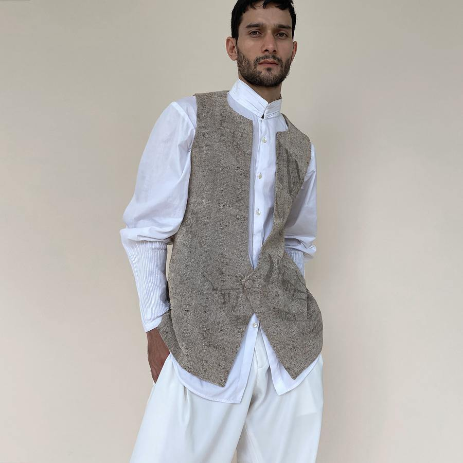 Handloom khadi bundi with single botton closure and shaped back. Cotton khadi shot texture bundi is ornamented with abstract distress print.  abhishek sharma, abhishekstudio