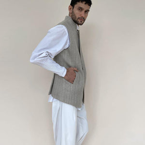 Shaped mandarin collar bundi with single button closure and concealed zipper. Heavy weight woven texture  linen bundi features double vents and shaped back for that extra ease while sitting and or on the go.  abhisheksharma , abhishekstudio