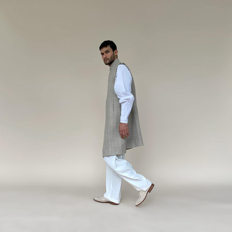 Shaped mandarin collar sherwani with front overlap closure. Heavy weight woven texture linen sherwani features square armhole and slightly layered panels for that extra ease while sitting and or on the go.  abhisheksharma , abhishekstudio