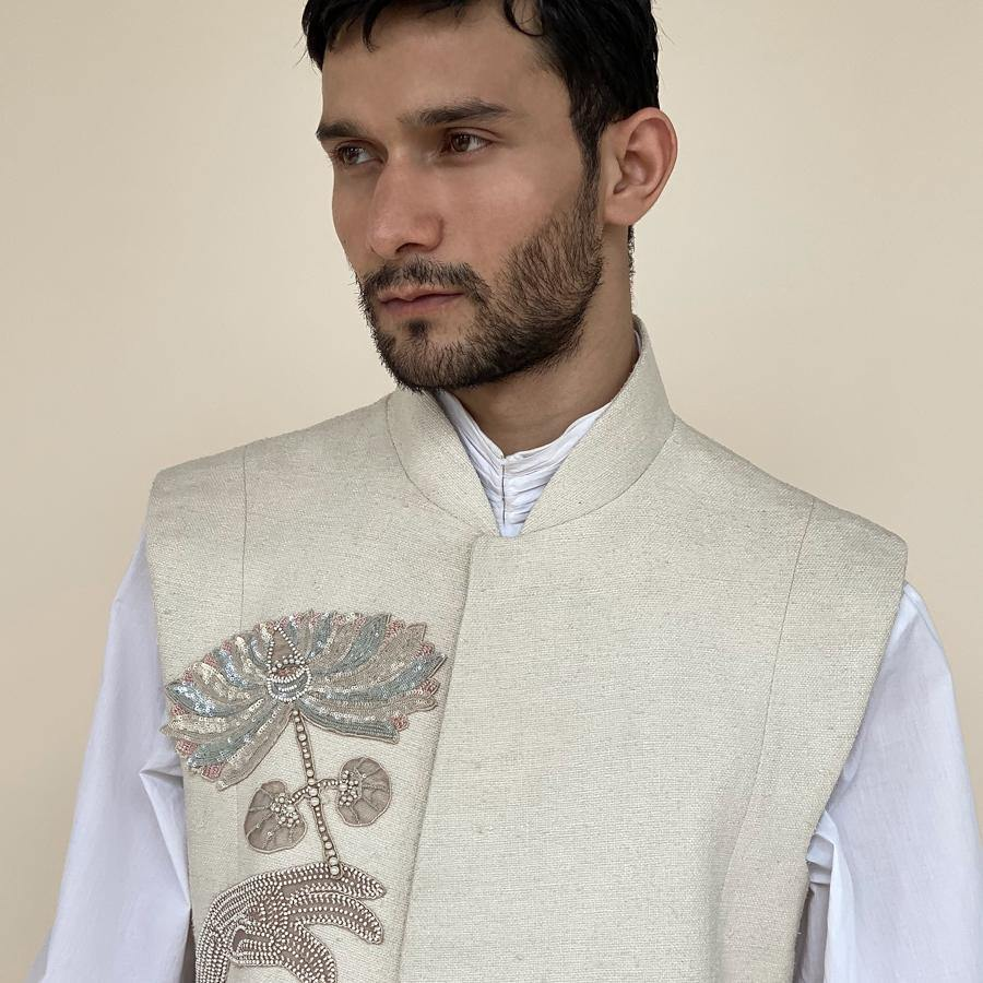 Sleeveless handloom silk sherwani with shaped mandarin collar. Heavy weight matka silk sherwani features overlapped front panels for that extra ease while sitting or on the go. Sherwani is embellished with sequin and pearl lotus appliqué.  abhisheksharma , abhishekstudio