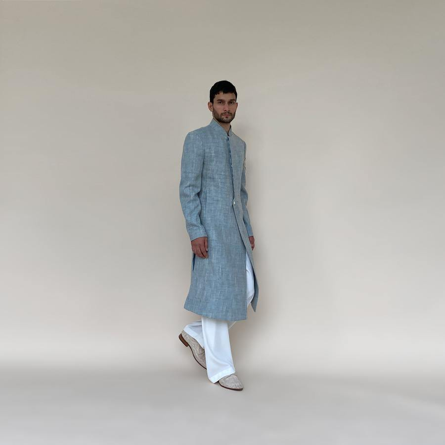 Shaped mandarin collar sherwani with single button front overlap closure. Heavy weight cotton khadi sherwani features high slits and slightly layered panels for that extra ease while sitting and or on the go. Sherwani is embellished with sequin and pearl lotus appliqué on the sleeve.  abhisheksharma , abhishekstudio