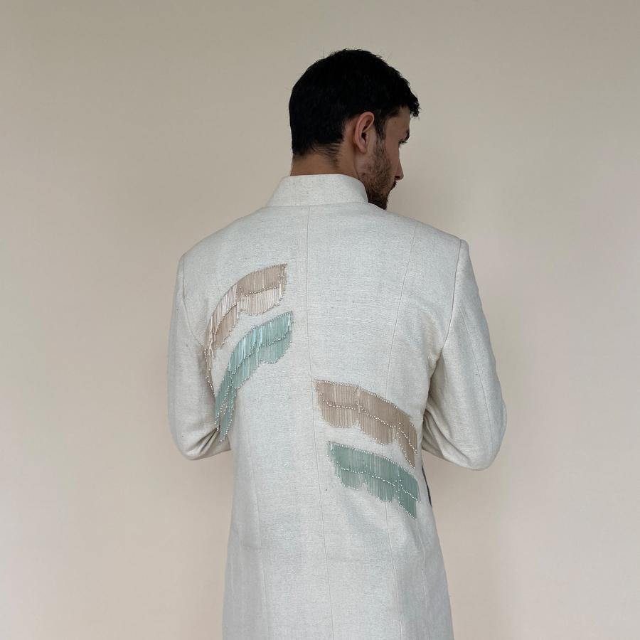 Shaped mandarin collar sherwani with mother of pearl buttons. Heavy weight handloom matka silk sherwani features high slits and slightly flared double princess panels for that extra ease while sitting and or on the go. Sherwani is embellished with palm leaf bugle bead embroidery in pastel colours.  abhisheksharma , abhishekstudio