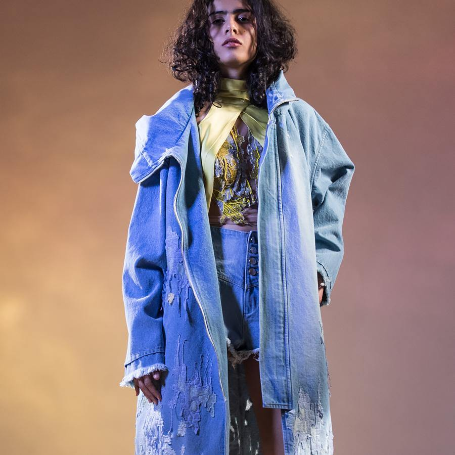 Washed and damaged boyfriend denim jacket with  worn out raw edge hem. Hooded oversized coat is frayed and ripped in abstract patterns around the hem. Mid-length unisex denim coat is embellished with impressionist embroidery appliqué and bugle bead detailing.  abhisheksharma , abhishekstudio