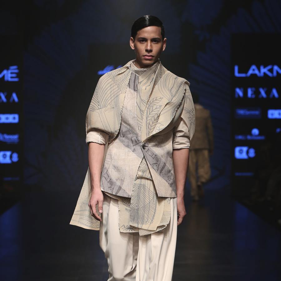 Matka silk bundi fastened with single botton closure and shaped back with double vents. Handloom silk texture is ornamented with abstract distress print in bias stripes. Structured bundi is meticulously styled over a cotton shirt with folded cuffs, then layered with a pin tuck texture forest print drape and draped baggy pants. A look that is perfect for the modern day groom who can slay. abhishek sharma, abhishekstudio
