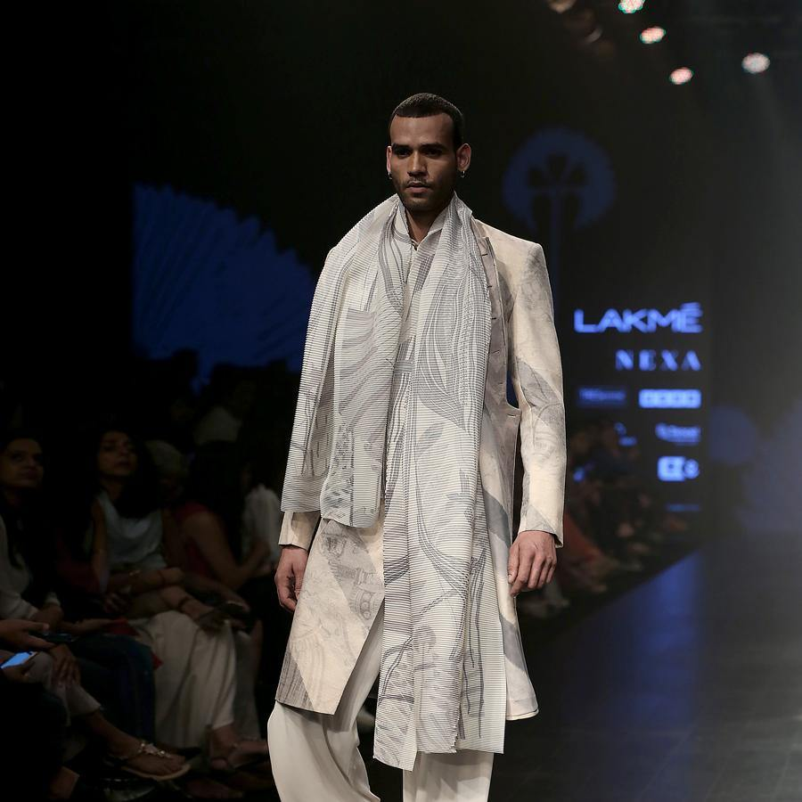 Short length single button closure sherwani with concealed placket. Cotton khadi sherwani is meticulously printed in abstract bias stripes and styled with draped wide pants, shirt and forest print textured stole. A look that is perfect for the modern day groom who slay and know how to carry the attitude.  abhisheksharma , abhishekstudio