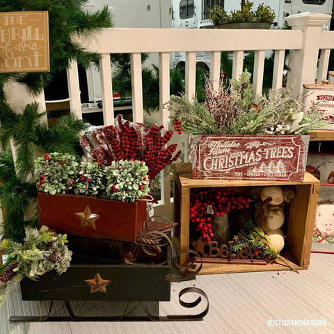A red Christmas sleigh, with lots of green florals, and a wooden crate filled with Christmas candles and greenery.
