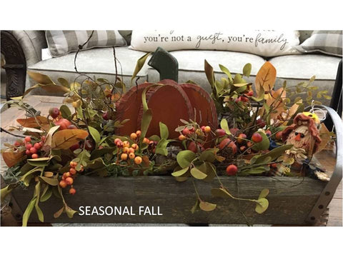 A wooden tray with iron handles is filled with orange, brown yellow and green florals. A wooden orange pumpkin is in the centre to celebrate fall.