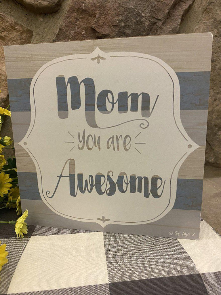 A lightweight box sign that says Mom you are awesome in the centre. It can be hung or sit on a shelf. The background of the sign is painted in grey and blue stripes. The stripes are visible through the lettering on the front.