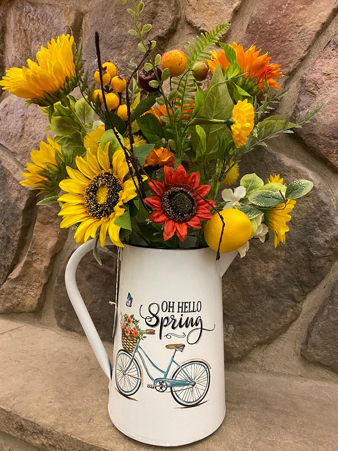 A white enamel pitcher is filled with beautiful sunflowers. The pitcher is white enamel, and has a white handle, and black painted trim around the top and spout. The picture on the side is of a blue vintage bike and says Oh Hello Spring.