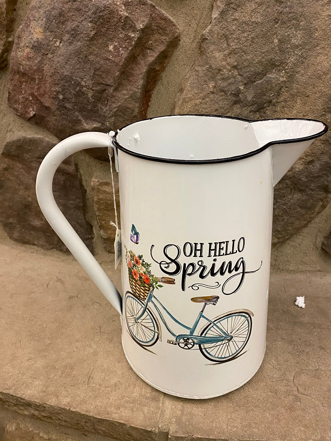 A close up of a white enamel pitcher. The picture on the side is of a blue vintage bike with a basked full of pink toned flowers and says Oh Hello Spring.