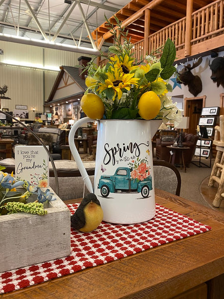 A white enamel pitcher is filled with beautiful sunflowers and lemons and sitting on a farmhouse style table. The pitcher is white enamel, and has a white handle, and black painted trim around the top and spout. The picture on the side is of a vintage blue truck filled with pink flowers and says Spring is in the Air.