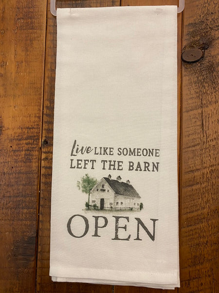 A cream coloured cotton tea towel has a printed message on it that says Live like someone left the barn open. There is picture of a white barn with a tree beside the words.
