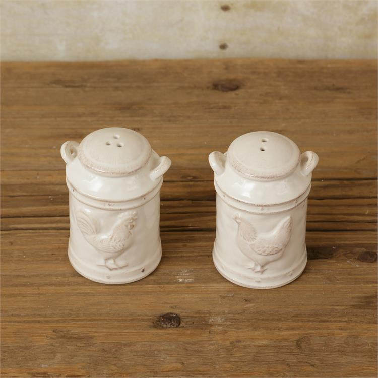 White salt and pepper shakers in the shape of milk cans. The salt shaker has an embossed rooster and the pepper shaker has an embossed chicken. The paint on them are slightly distressed.  are made of ceramic
