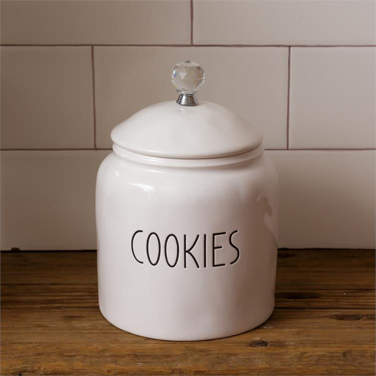 White, farmhouse style ceramic cookie container. It has a glass knob on the white ceramic lid. The word Cookies is on one side of the container.