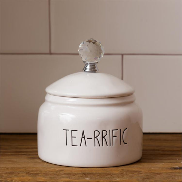 White, farmhouse style ceramic tea container. It has a glass knob on the white ceramic lid. The words Tea-rrific are on one side of the container.
