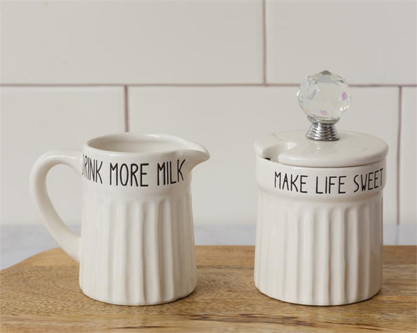 White farmhouse inspired cream and sugar set. The body of both pieces are ridged and the rim around the top of each has black lettering. The milk jug say Drink more milk and the sugar bow says make life sweeter. The lid on the sugar bowl has a glass knob.