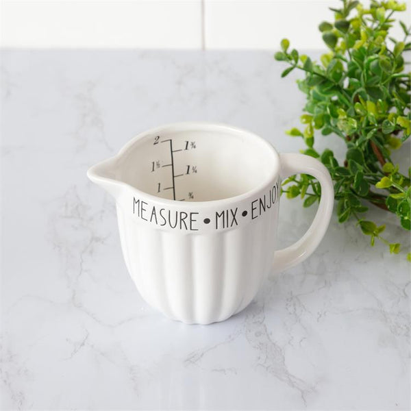 A white ceramic measuring cup that is a two cup size. The measure marks are in black on the inside of the cup. Around the outside rim of the cup are the words measure, mix and enjoy in black lettering. The cup has a handle and spout for easy pouring.